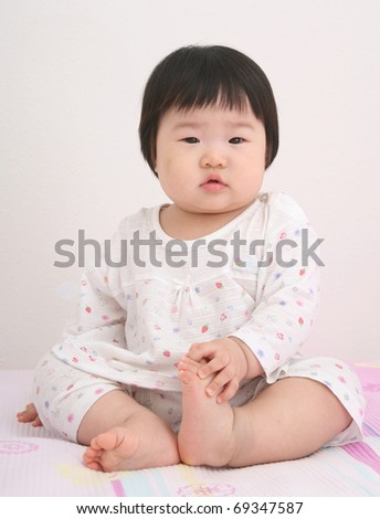 Beautiful nine month old baby asian infant girl in white body suit looking cute and grabbing foot with hand on bed - stock photo