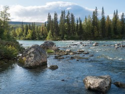 Beautiful northern landscape with azure blue river Kamajokk, mountains, boulders and spruce tree forest in Kvikkjokk in Swedish Lapland. Summer sunny day, white clouds