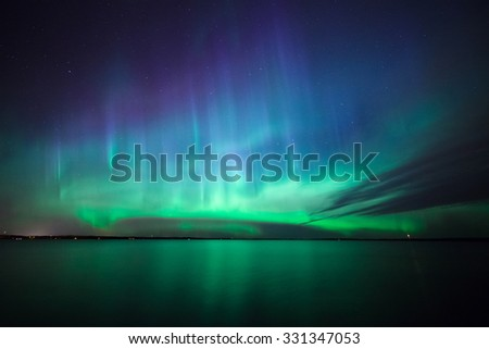 Beautiful northern lights aurora borealis over lake in finland #331347053