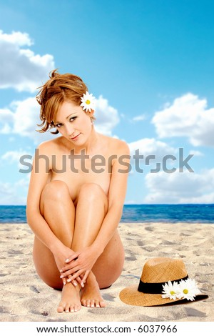 stock photo : beautiful nude girl at the beach smiling and sitting on the ...