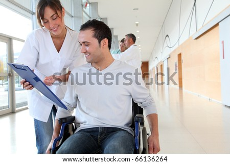 Beautiful nurse standing by man in wheelchair