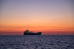 Beautiful  ocean sunset, with colorful clouds, blue ocean and silhouette of ship, oil tanker on the horizon.