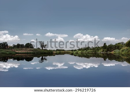 Beautiful of nature - The photo of pastel blue minimal picture with reflection of trees , cloudy sky like a mirror on the water  from countryside of thailand in square
