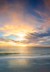 Beautiful of panorama vertical sunset over the clam sea with cloud sky background. Sunset over tropical beach. Nature summer  concept. Peak sunset over sea with yellow light reflect on sea water.