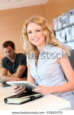 Beautiful office worker using tablet in office