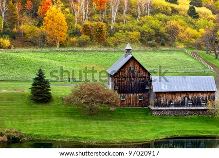 Beautiful old barn in a green meadow and trees with colorful fall leaves