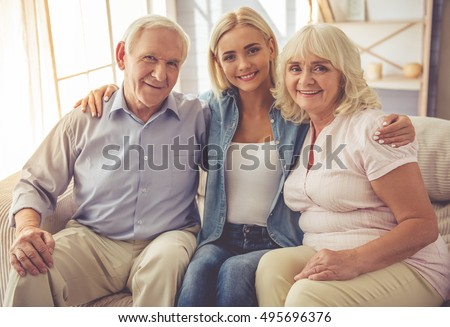 Beautiful old couple and young girl are hugging, looking at camera and smiling while sitting on couch at home