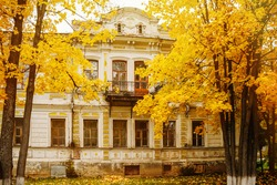 Beautiful old house and autumn yellow trees, antique building