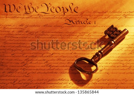 Beautiful old key on a copy of the US constitution with warm tungsten light.
