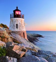 Beautiful old lighthouse on rocks at sunset