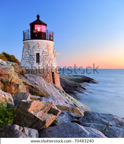Beautiful old lighthouse on rocks at sunset