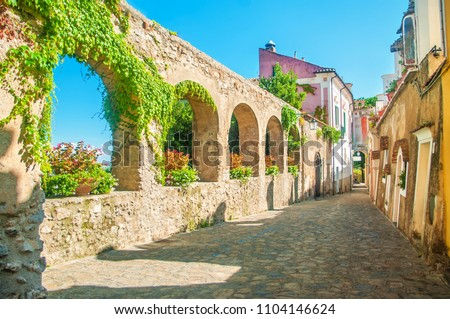 beautiful old stone wall with arches and flowers on old european street, Ravello, Amalfi coast, Italy #1104146624