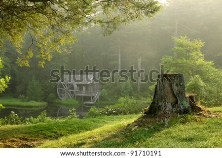 Beautiful old watermill building in lush forest on dewy morning