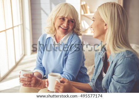 Beautiful old woman and young girl are drinking tea, talking and smiling while sitting on couch at home #495577174