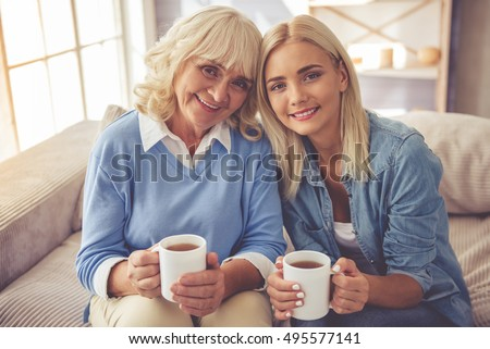 Beautiful old woman and young girl are holding cups of tea, looking at camera and smiling while sitting on couch at home #495577141