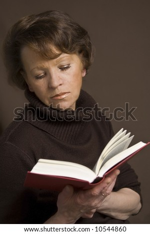 Beautiful old woman in brown sweater on a dark background - stock photo