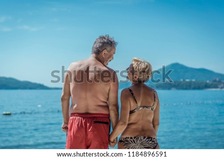 Beautiful older couple in love on vacation enjoying the summer time on beach