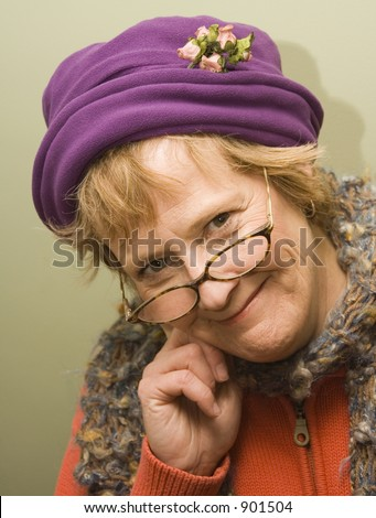 Beautiful older woman with a fun expression wearing a purple hat and red sweater.