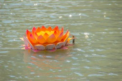 Beautiful orange kratong is floating on the water. Conccept for loy kratongs festival celebrated in Thailand.