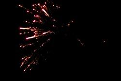Beautiful orange single exploding firework against black sky background on new years eve