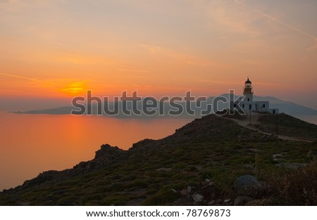 Beautiful orange sunset in the sea and the lighthouse on the island of Mykonos. Greece.