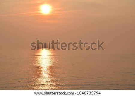 Beautiful orange sunset over Baltic sea with sunlight reflection on water. The sunbeams through fog creating a mystic atmosphere. #1040735794