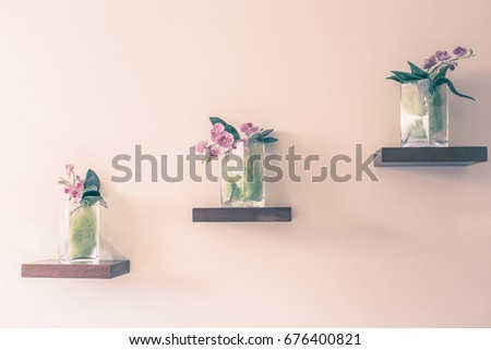 Beautiful orchid in glass vase on shelf on the wall background. Vintage color tone. #676400821