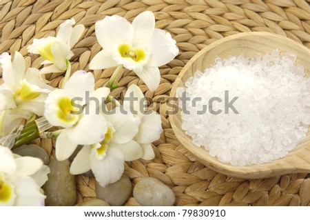 beautiful orchid with pebble and bath salt in wood bowl on woven mat