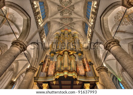 Beautiful organ, catched in a symmetrical shot with big pillars in the main church in Breda, Netherlands
