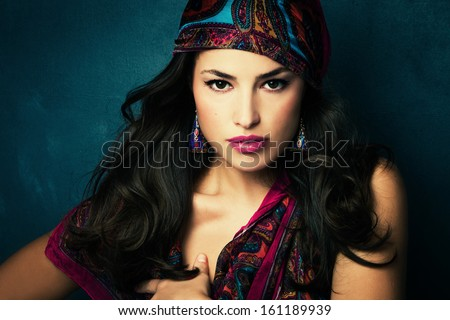 beautiful oriental look young woman with scarf on blue background