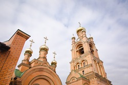 Beautiful orthodox church in Kiev, Ukraine. Old ancient architecture building. White ancient bell tower with green roof in spring time. Temple of Mother Alipia in Kyiv on backdrop of cloudy sky