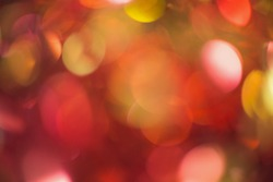 Beautiful out of focus round lights background of red, orange, yellow, golden, pink and black colors