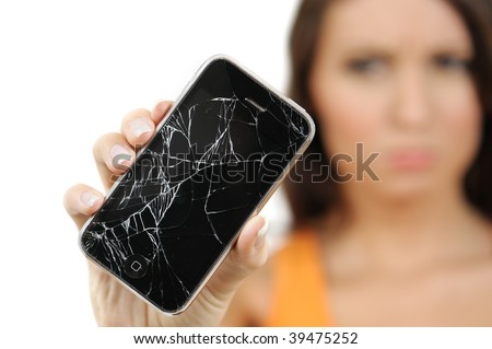 Beautiful, out of focus, young woman with troubled expression holding out her broken touch screen mobile phone