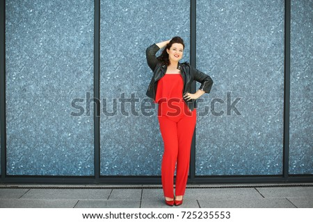 Shutterstock Beautiful overweight woman in red pantsuit standing on city street