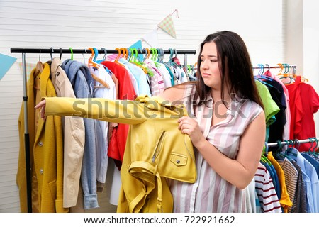 Beautiful overweight woman trying to put on small-sized jacket at store