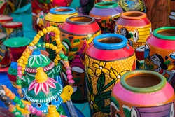 Beautiful painted colorful terracotta pots, works of handicraft, for sale during Handicraft Fair in Kolkata. Vertical image.