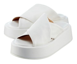 Beautiful pair of snow-white flip-flops made of genuine white leather with criss-cross stripes and a massive high sole. The trend of the season. High quality photo.