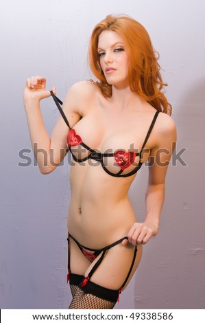 Beautiful pale redhead in skimpy black lingerie - stock photo