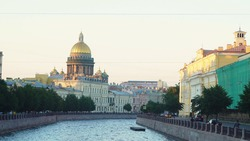 Beautiful panorama of city canal with beautiful architecture and domed Cathedral. Media. Landscape of old city with canal and Cathedral with dome in evening sun. View of St. Isaac's Cathedral