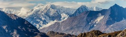 Beautiful panorama of massive mountains and snowy peaks covered with white clouds. Glacier Bay National Park. Alaska, USA