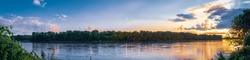 Beautiful panorama of Missouri River at sunset in summer; woods in background