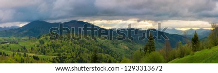 beautiful panorama of mountainous countryside. wonderful springtime landscape. forested rolling hills. overcast sky with sun rays in the distance