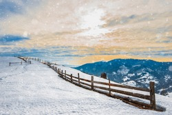 Beautiful panorama of the mountain ranges covered with snow and divided into hiking trails overlooking the cloudy sky and sunset. Place for advertising. Mountain tourism concept