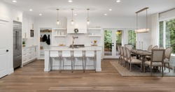 Beautiful panorama of white kitchen and dining room in new luxury home, with pendant lights, dining room table and chairs, kitchen island, and counters