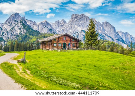 Beautiful panorama view of idyllic rural mountain scenery in the Alps with traditional old alpine mountain hut and fresh green meadows on a sunny day with blue sky and clouds in springtime