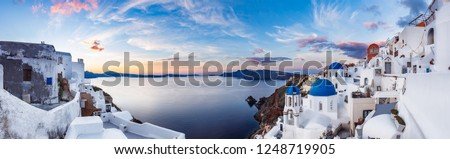 Beautiful panorama view of Oia village on Santorini island in Greece at sunrise with dramatic sky.