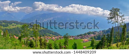 Beautiful panorama with traditional huts with tile roof and Lake Thun (Thunersee) on the slope of the forest-covered mountains in the Swiss Alps on a sunny day. Beatenberg, Switzerland