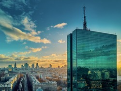 Beautiful panoramic aerial drone view to the Center of modern Warsaw city with silhouettes of skyscrapers in in the rays of the setting winter January sun - amazing sunset, Poland