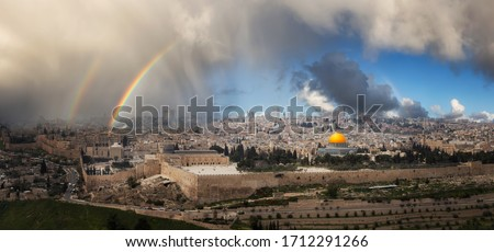 Beautiful panoramic aerial view of the Old City, Tomb of the Prophets and Dome of the Rock. Dramatic Rain and Rainbow Sky Composite. Jerusalem, Capital of Israel.