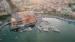 Beautiful panoramic aerial view photo from flying drone at sunset to Bari Apulia City port boats and yachts Sea Coastline, Teatro Margherita, and Bari city skyline. Bari ,Apulia, Italy (Series)